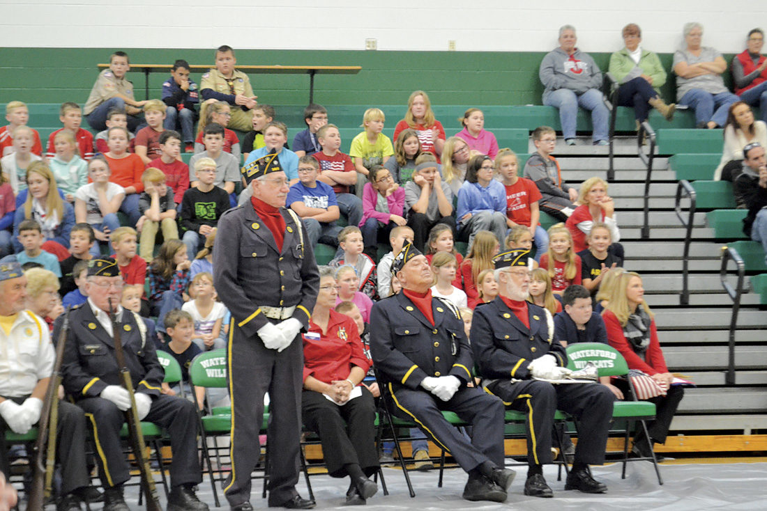 Photo by Michael Kelly A veteran stands as service branch anthems are played while students at Waterford Elementary School do a presentation at the school's tribute to veterans Thursday.