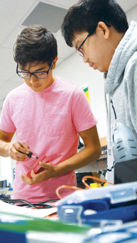 Photo by Michael Erb Joseph Madrid, left, and Thinh Tran, right, both seniors at Parkersburg South High School, work on an accelerator button for a battery-power, rideable toy car which is being modified as a therapeutic vehicle for a child with special needs as part of the Caperton Center's Go Baby Go! program.