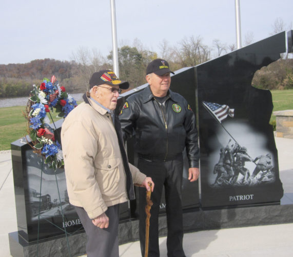 Photo by Wayne Towner U.S. Army veterans Junior Ray Linch, left, and Rick Raab place a wreath at the Gold Star Memorial at Spencer's Landing in Vienna on Saturday. The two men are among those featured on the memorial, which was dedicated just after Veterans Day 2016 and served as the location for Saturday's Vienna Veterans Day service.