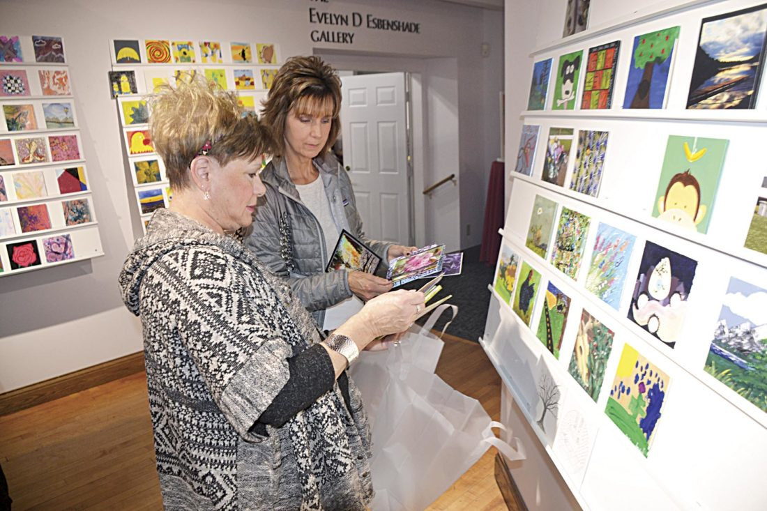 """Photo by Brett Dunlap Jan Crego, of Parkersburg, and Kyra Smith, of Parkersburg, try to decide on which pieces of art they wanted to buy Sunday during the """"6 x 6: The Next Small Thing in Art"""" show and sale at the Parkersburg Art Center."""