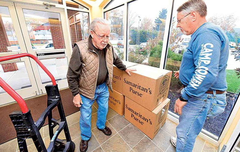 Bill Holbert, left, and Steve Metheny take a break after moving six boxes of Operation Christmas Child shoeboxes to the loading entrance of Emmanuel Baptist Church Monday. (Photo by Jeff Baughan)