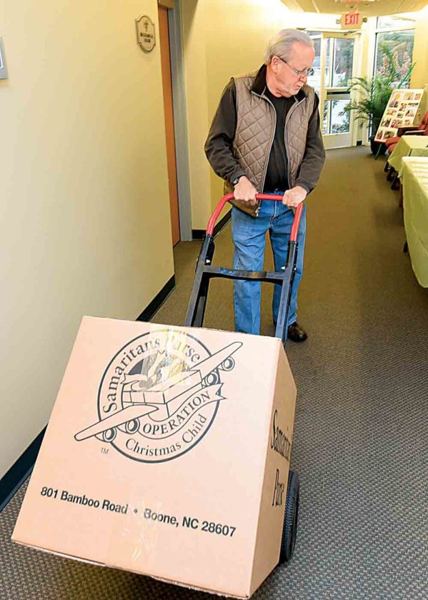 Bill Holbert takes a box loaded with Operation Christmas Child shoeboxes to the loading entrance of Emmanuel Baptist Church Monday. (Photo by Jeff Baughan)
