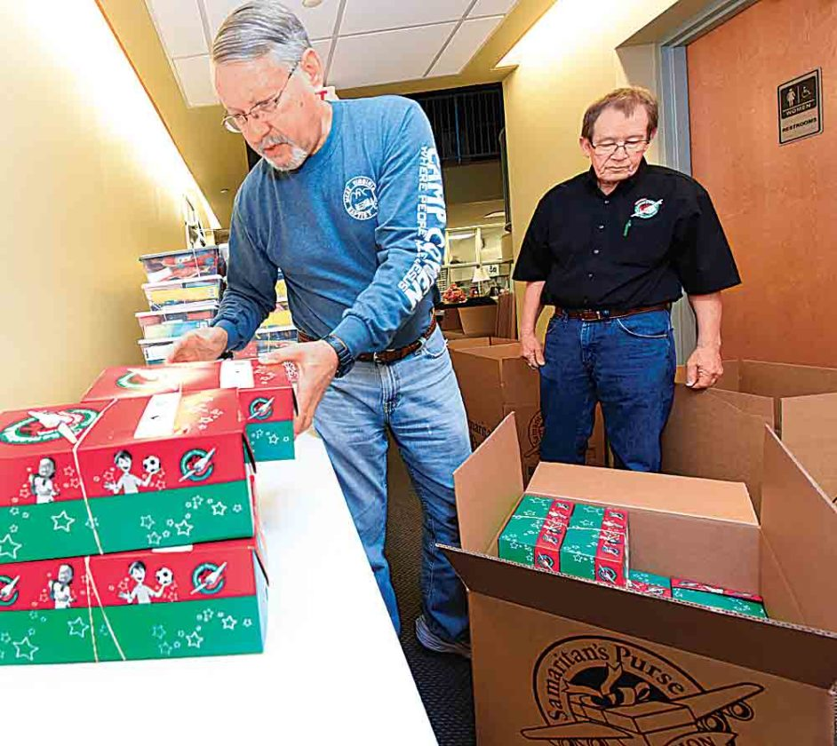 Steve Metheny, left, grabs another shoebox to load as he and Evan Frees work at filling a shipping box for Operation Christmas Child Monday at Emmanuel Baptist Church during the first day of collections. (Photo by Jeff Baughan)