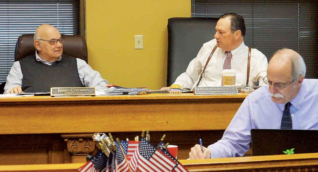 Wood County Commission member Jimmy Colombo, left, and commission President Blair Couch, right, along with County Administrator Marty Seufer, front, talk during Monday's commission meeting. The commission says it will reschedule a presentation to state officials concerning the final cost of the IEI Plastics warehouse fire. (Photo by Michael Erb)