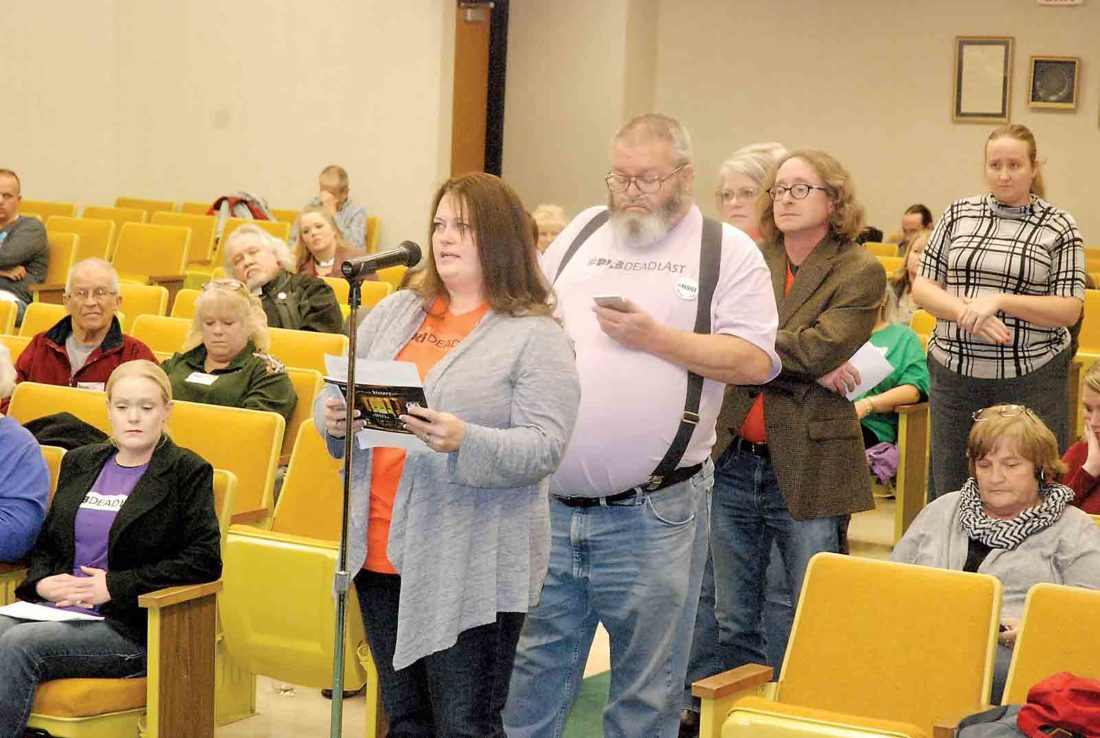 Parkersburg resident Jennifer Bryant, standing, left, continues a statement from members of Fairness Parkersburg during Tuesday's Parkersburg City Council meeting as fellow supporters Rodney Wilson of Walker, Jeanne Peters of Vienna and Eddie McDonough of Parkersburg wait their turn. (Photo by Evan Bevins)