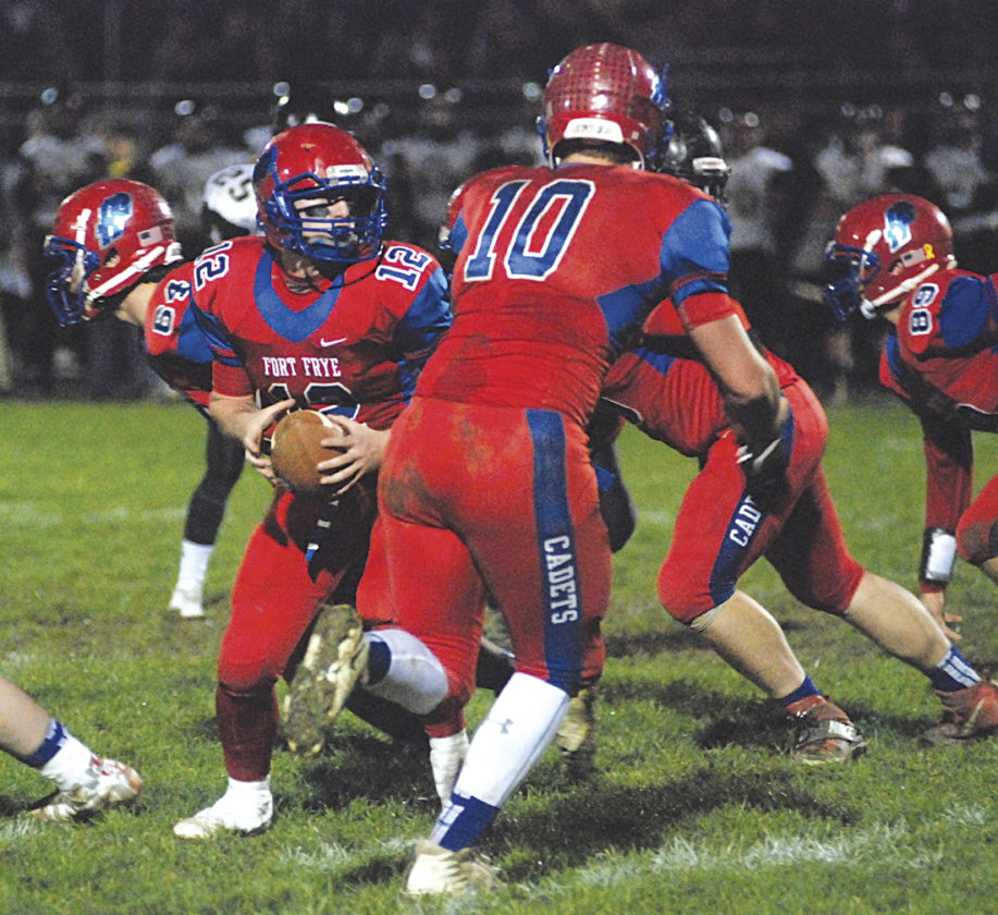 Fort Frye's Tate Engle (12) fakes a handoff to teammate Tyler Bradford (10) during a high school football playoff game against Northmor earlier this season in Beverly. Engle and Bradford were two of the Cadets' 11 All-East District honorees Tuesday. Photo by Jordan Holland.