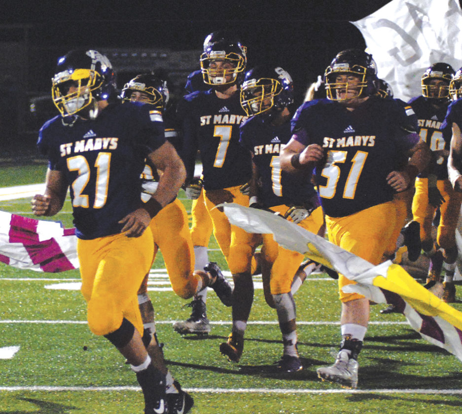 The St. Marys squad rushes the field during a high school football game earlier this season. Photo by Jay W. Bennett.