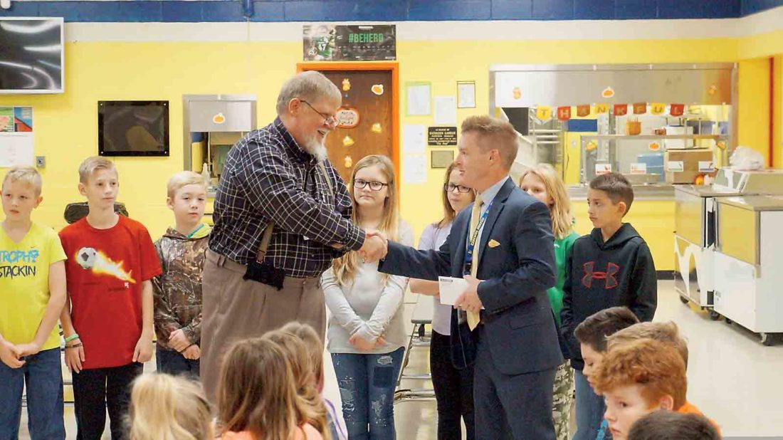 Photo by Michael Erb Rich Fullmer, left, district manager for Dollar General, presents a $10,000 literacy grant check to Kanawha Elementary School Principal Matt Null and members of the school's 5th-grader leadership team.