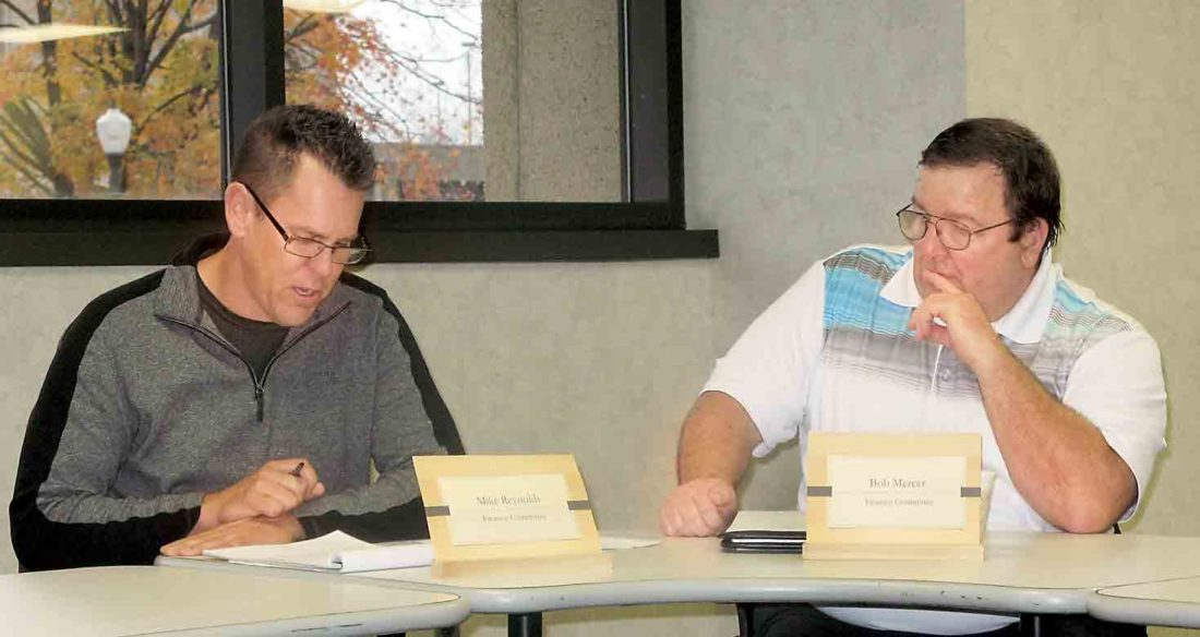 Photo by Evan Bevins Parkersburg City Councilman Mike Reynolds, left, reads a statement on potential personnel cuts as Councilman Bob Mercer listens during a council Finance Committee meeting Thursday at the Municipal Building.