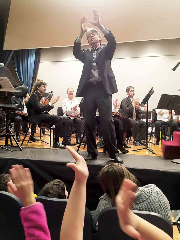 Photo Provided Conductor Grant Cooper leads students in pantomiming spinning straw into gold.