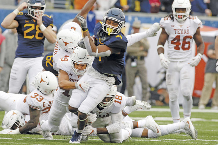 West Virginia running back Kennedy McKoy (4) is tackled by Texas defensive backs Davante Davis (18) and Brandon Jones (19) during the second half of an NCAA college football game Saturday in Morgantown. Texas defeated West Virginia 28-14.