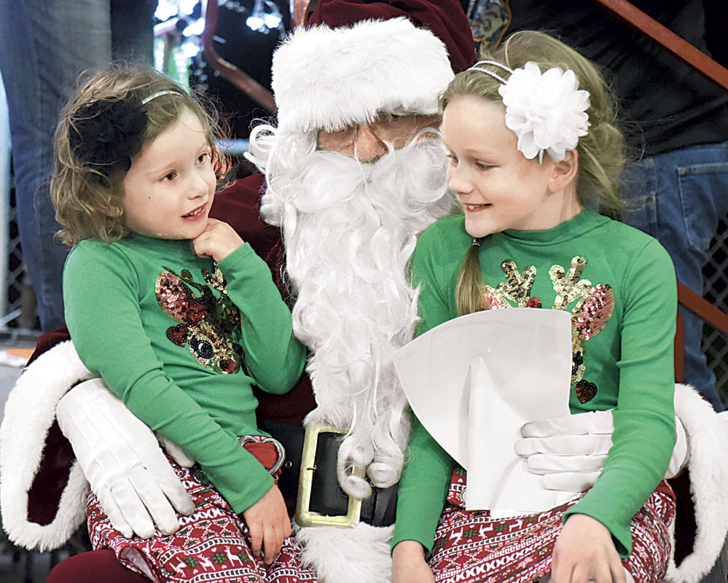 Photo by Jeff Baughan Serra Alford, a kindergarten student at Emerson Elementary School, left, sits on Santa's lap with her sister, Alexis Alford, right, a second grader at the school. Alexis received an award in the Holiday in the Park coloring contest.