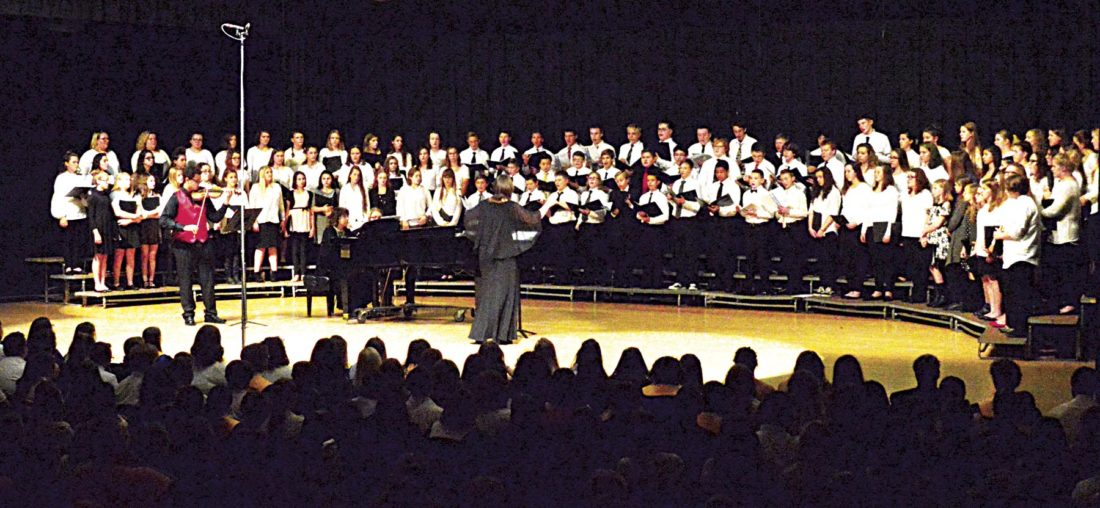 Photo by Doug Loyer Ann Lillie-Briggs directs the Middle High School Honors Choir on the Warren High School auditorium stage.