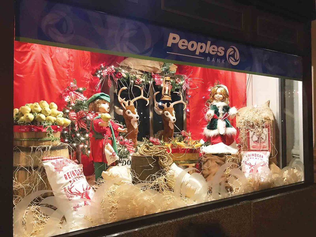 Photo by Janelle Patterson The Second Street windows of Peoples Bank in Marietta shine onto the dark street Tuesday with holiday cheer from Santa's reindeer.