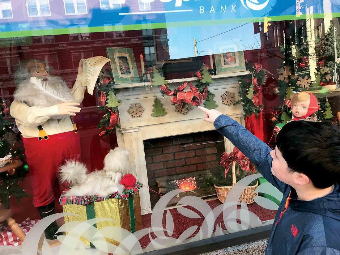 Photo by Janelle Patterson Frederick Nicely, 12, of Williamstown, points out Mrs. Claus on the mantle of the fireplace in the Peoples Bank holiday display in Marietta Tuesday.