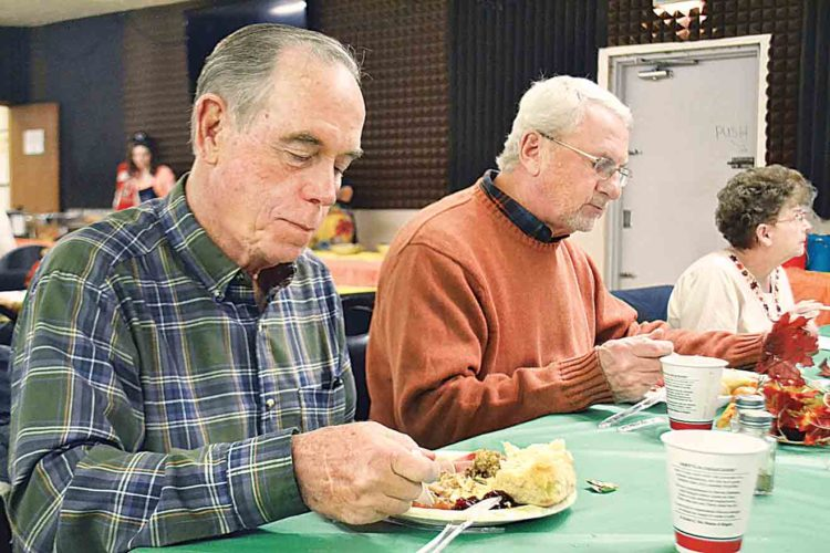 File Photo Williamstown residents Tom Rowell, 74, and Bruce Holmes, 69, enjoy the community Thanksgiving dinner hosted by American Legion Post 159 in Williamstown last year.