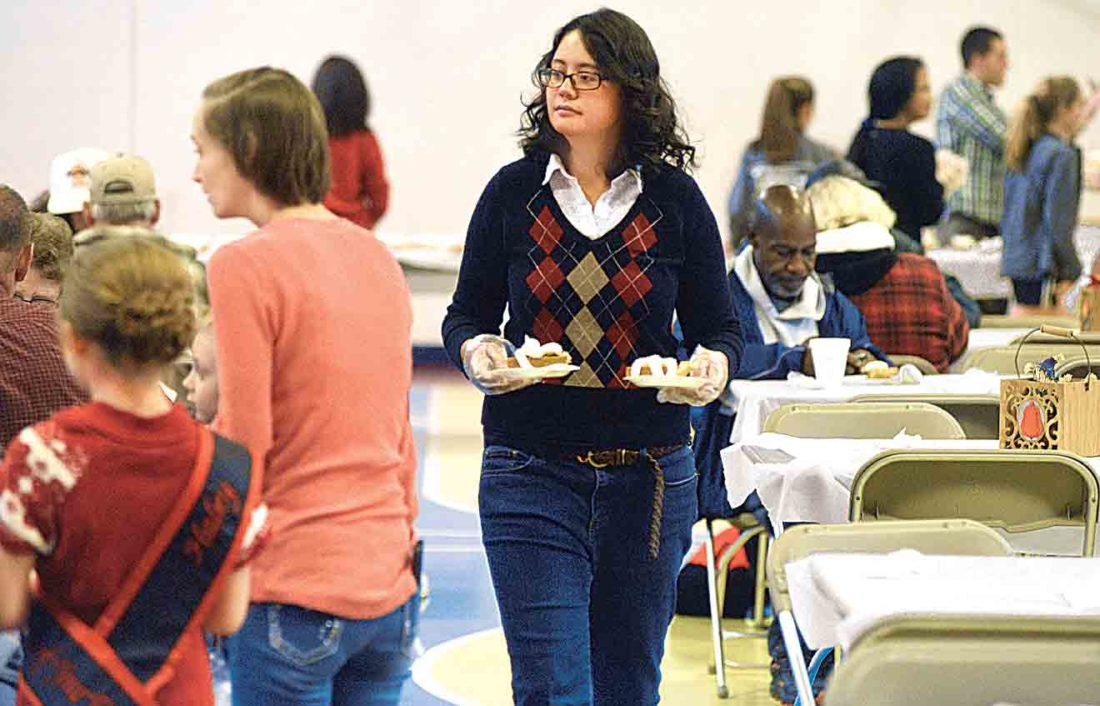 File Photo Volunteer Michelle Jacobs helps serve food at last year's Salvation Army dinner on Thanksgiving.