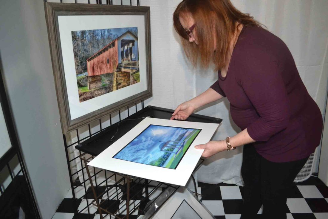 Photo by Erin O'Neill Deb Lorentz, a photographer from the Veto area, places a mat around a photo she took in Parkersburg on Monday. Lorentz will have several of her photos for sale at the Marietta High School Band Boosters craft show Saturday at the fairgrounds.