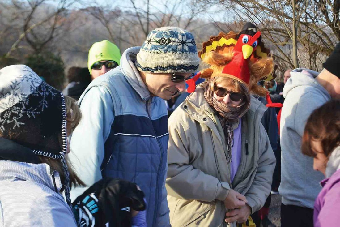 Jennifer Schenkel, right, takes registration information from participants in the second annual Devola Turkey Trot. Schenkel led event organization for the East Muskingum Civic Association. (Photo by Michael Kelly)