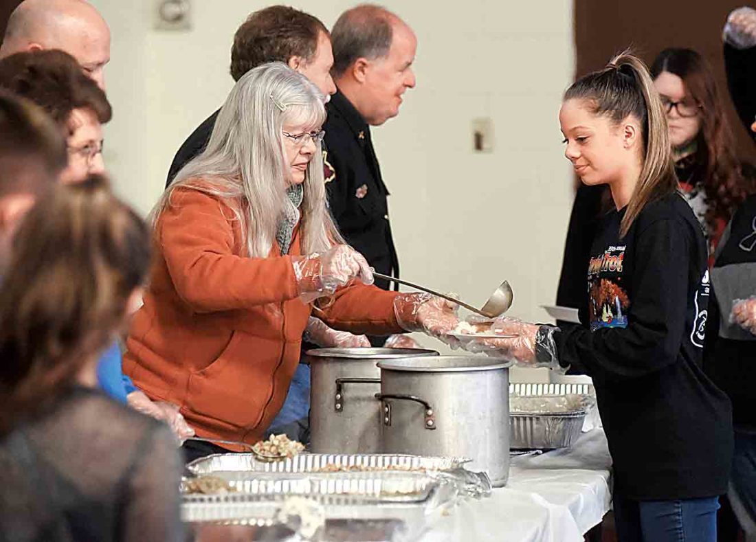 Bonnie Taylor, left, pours gravy on a plate for volunteer Sofia Strobl, prior to her taking the plate to a visitor to the annual Thanksgiving Day meal. (Photo by Jeff Baughan)