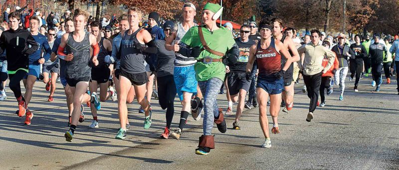"Wade Sullivan, dressed as Link from the video game series ""The Legend of Zelda,"" runs near the front of the pack following the start of the three-mile, 39th annual Parkersburg Turkey Trot in City Park. Eventual winner Johnny Hogue, with the jersey reading ""Richmond,"" follows closely behind him. (Photo by Jeff Baughan)"