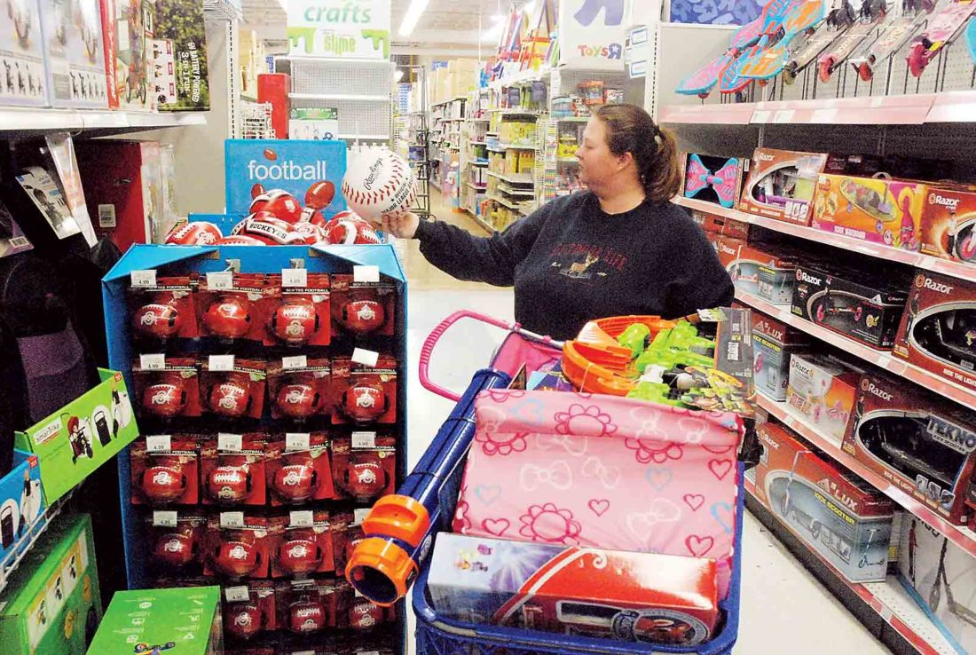 Photo by Evan Bevins Racine, Ohio, resident Stacy Marcinko looks at items to add to an already full cart Friday morning at Toys R Us in Vienna.