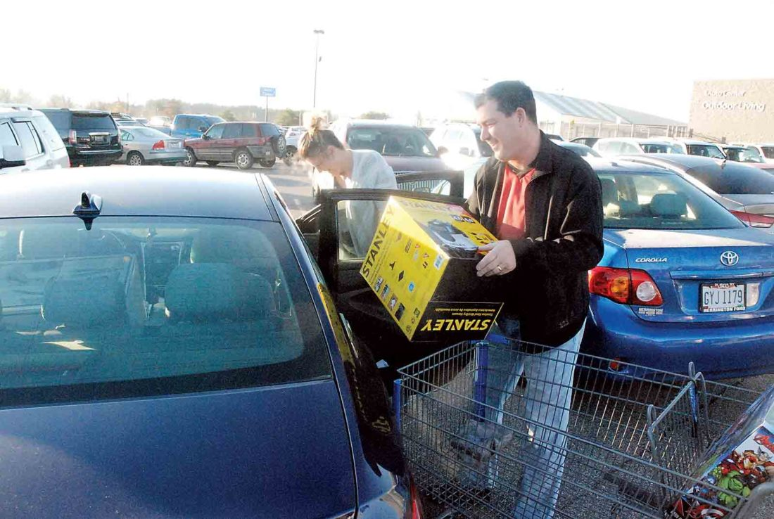 Photo by Evan Bevins Mineral Wells residents Lisa and Tim Whitehair load their car after making their second bargain-hunting stop at the south Parkersburg WalMart in less than 24 hours Friday morning.