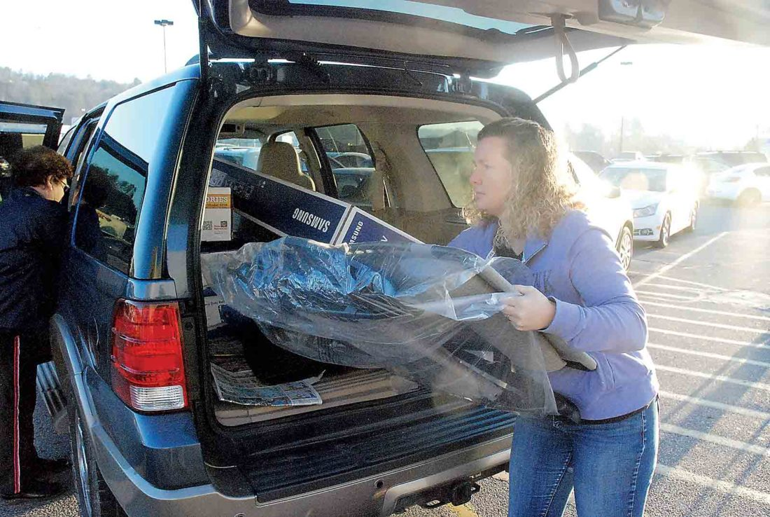 Photo by Evan Bevins Ripley resident Dawna Rose rearranges some of the items she and her mother picked up during their Black Friday shopping at the WalMart in south Parkersburg.