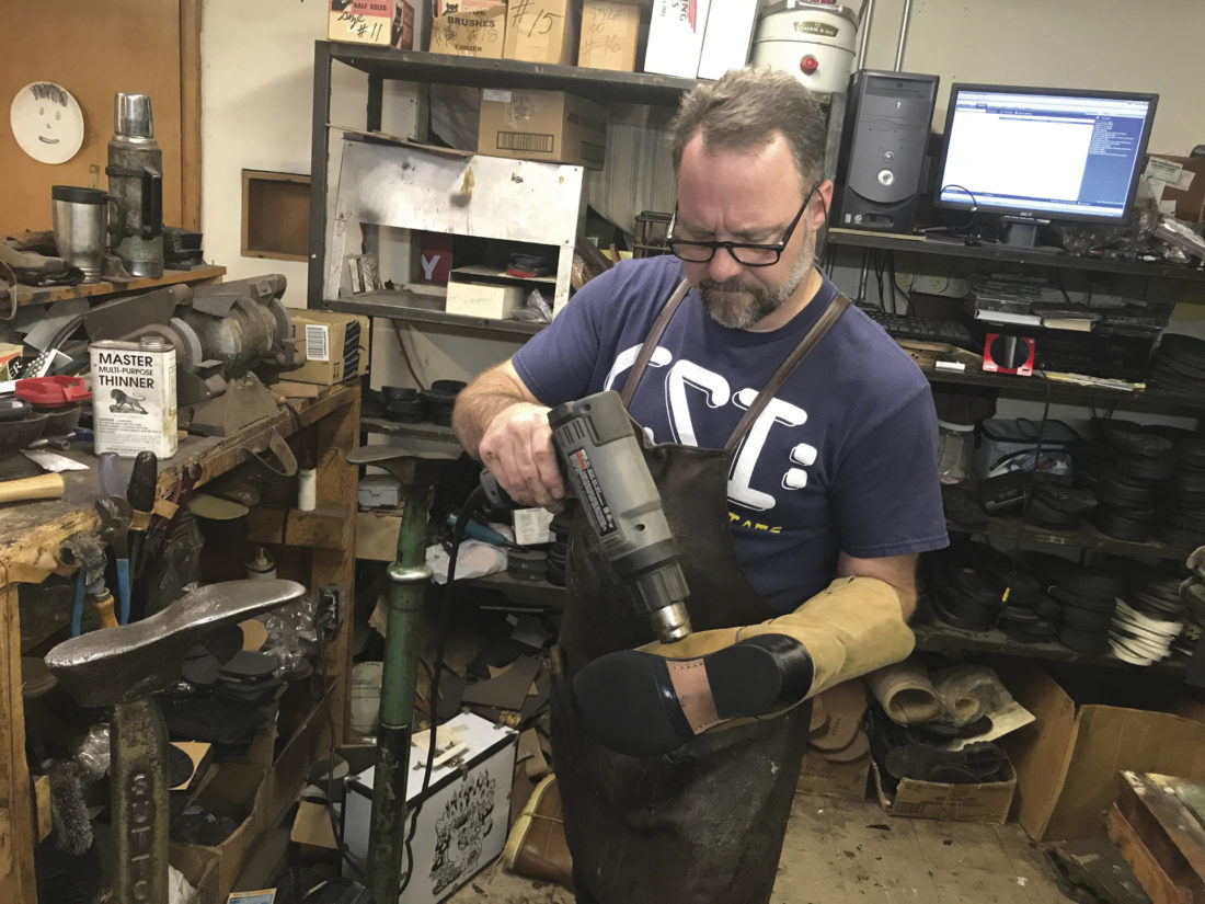 Photo by Janelle Patterson Bill Gossett, 47, of Marietta, uses a heat gun on a cowboy boot while in his shop, Cobbler John's, located in the basement of the old Dime Bank building in Marietta. The heat gun sets the polish on the new welt and sole.