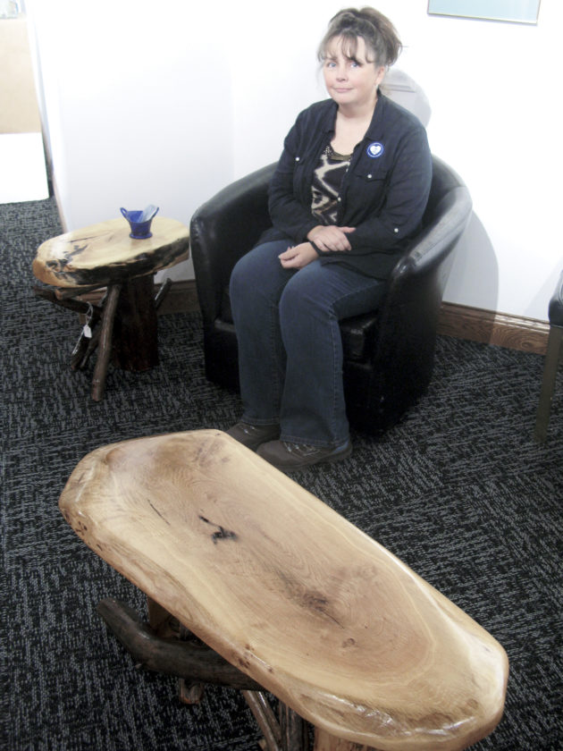 Photo by Jeffrey Saulton Maria Richard, of Spencer, shows some of the tables she made from Ohio River driftwood at the Parkersburg Art Center. She said she gets tops for her tables and benched from a lumber yard. She began making them five years ago.