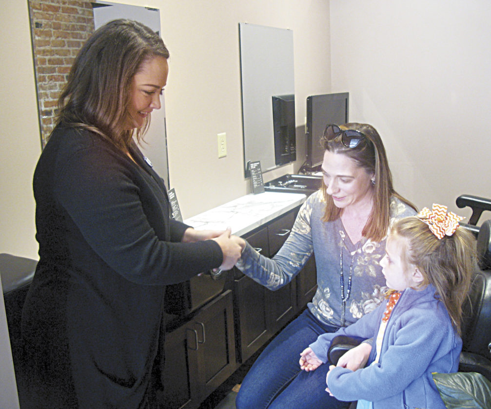 Photo by Jeffrey Saulton Laura Lowther, left, performs a hand massage for Kristin Meeks, center, as her daughter Caroline, right, watches at the Aspire Salon on Market Street in Parkersburg during Shop Small Saturday.