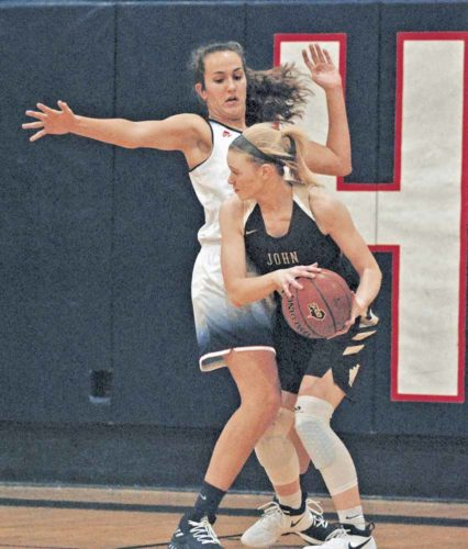 Parkersburg South's Makenna Winans, who poured in a career-high 38 points during the Patriots' 74-41 season-opening victory Tuesday night against John Marshall inside the Rod Oldham Athletic Center, stops the drive of Monarch guard Grace Frohnapfel. Photo by Jay W. Bennett.