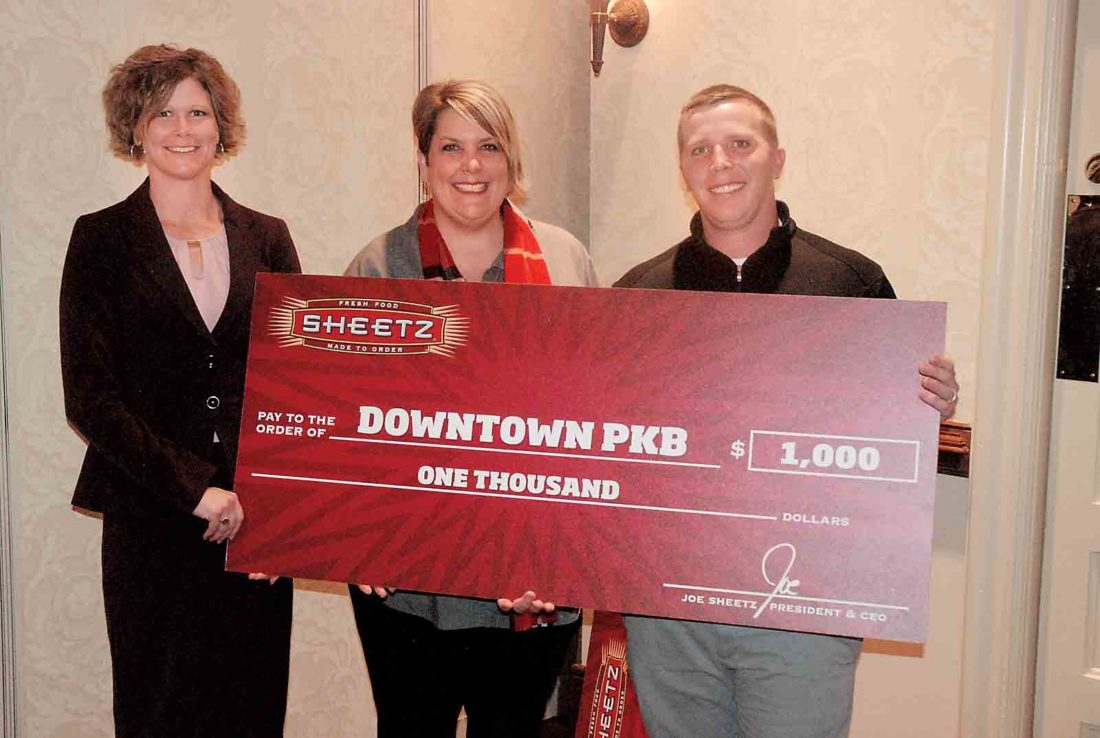 From left, Downtown PKB Board of Directors President Lindsey Anderson, Downtown PKB Executive Director Wendy Shriver and Sheetz representative Nic Ridenhour hold a $1,000 check representing Sheetz's contribution to Downtown PKB's Partner Program Wednesday at the Blennerhassett Hotel. (Photo by Evan Bevins)