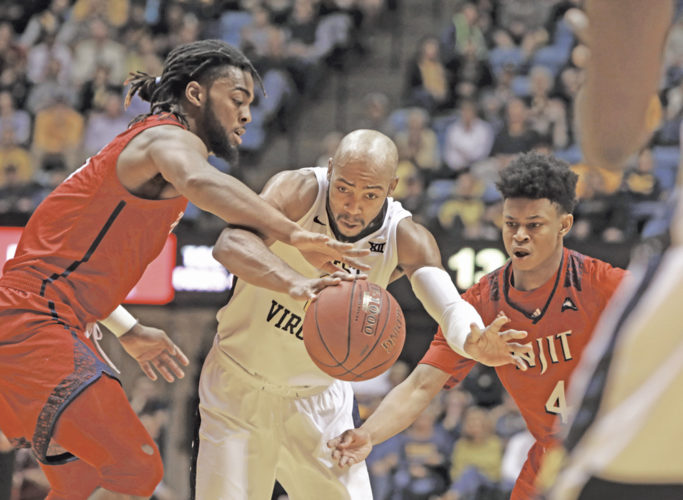 West Virginia guard Jevon Carter (2) passes the ball while defended by NJIT forward Abdul Lewis, left, and guard Zach Cooks (4) during the second half of an NCAA college basketball game Thursday in Morgantown.