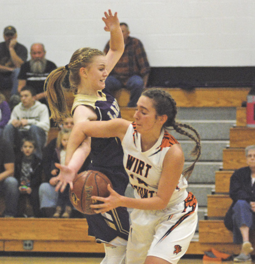 Wirt County's Taylor Anderson gets tied up with Addie Furr of St. Marys during Thursday night's season opener for both teams in Elizabeth. The Blue Devils used a big fourth quarter to leave town with a 54-26 triumph. Photo by Jay W. Bennett.