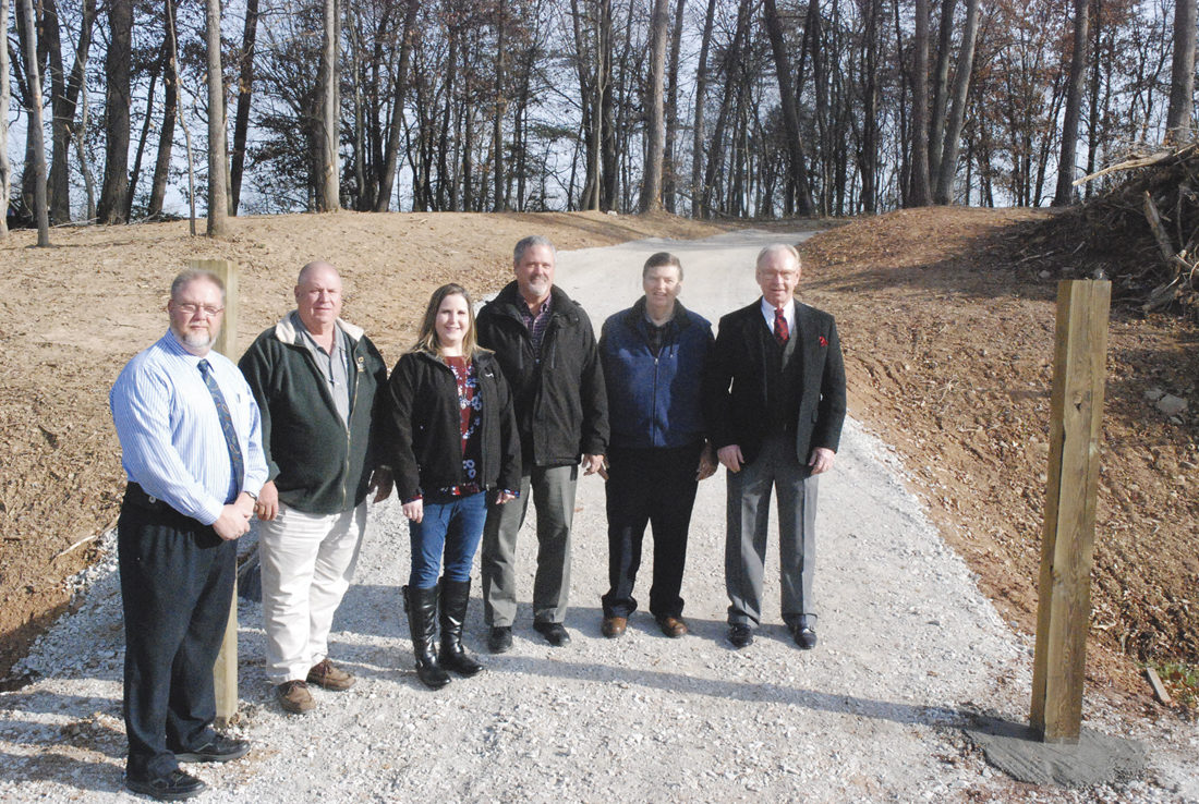 Photo by Evan Bevins From left, Wood County Schools Assistant Superintendent Mike Fling, Parkersburg Public Works Director Everett Shears, J.C. Bosley Construction Inc. representative Tessa Bosley-Stull, City Engineer Justin Smith, City Councilman Dave McCrady and Wood County Schools Superintendent John Flint pose for a photo Thursday at the foot of a walking path built by Bosley and city employees to connect Martin Elementary School with the Reserve at Edison Hill housing development.