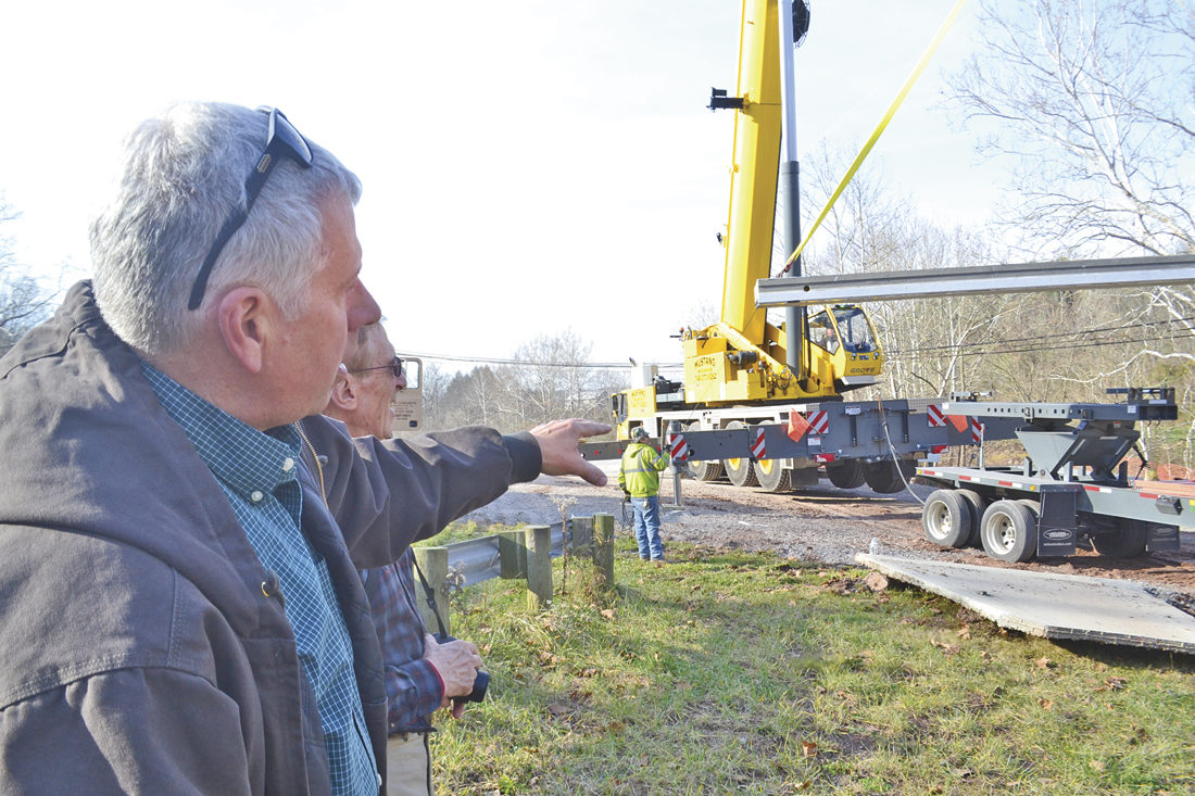 Photo by Michael Kelly George Broughton of the Broughton Foundation gestures as he talks to George Banziger from the foundation's trail committee as the two watch concrete slabs being placed to form a new bridge that will allow better access from the parking area onto paved trails on the Broughton Nature and Wildlife Education Area near Devola.