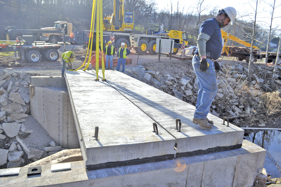 Photo by Michael Kelly Doug Lowe of Lowe Construction and Excavating checks a freshly positioned concrete slab as crew members work on the new East Bridge of the Devola Multi-Use Trail.