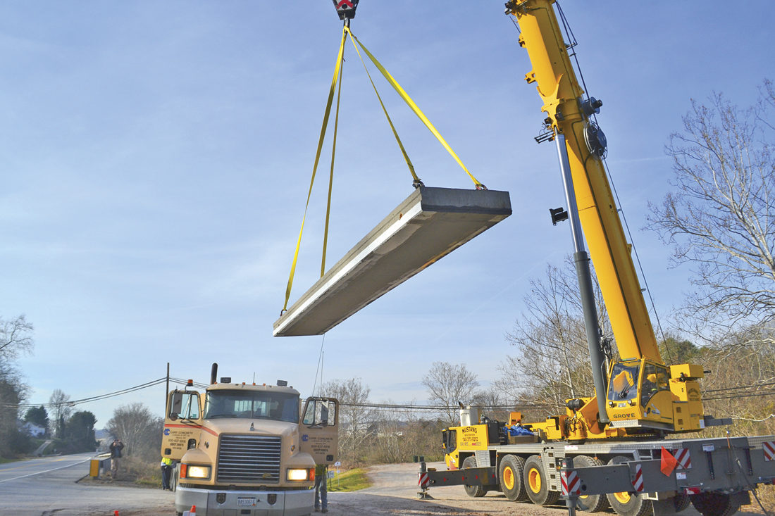 Photo by Michael Kelly A 225-ton crane from Mustang Aerial Services in Marietta lifts a 16,000-pound concrete slab for placement as part of the new East Bridge on the Devola Multi-Use Trail on the Broughton Nature and Wildlife Education Area Thursday morning.