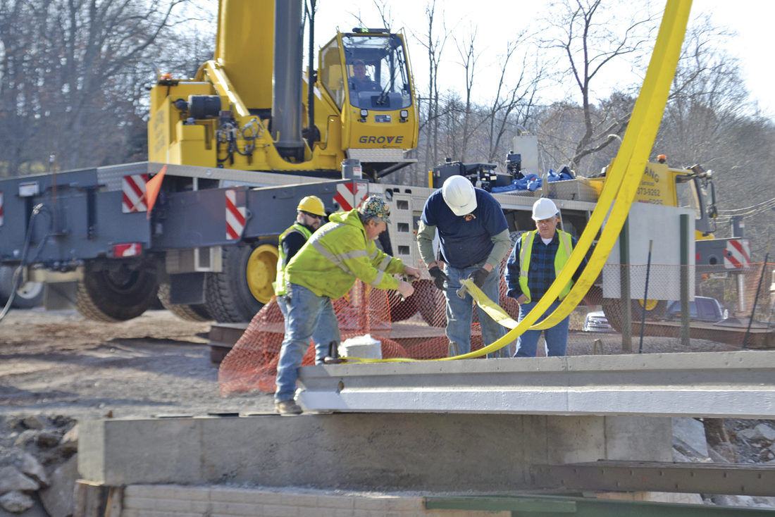 Photo by Michael Kelly Crews work to position 16,000-pound concrete slabs being lowered by a crane to form the new East Bridge of the Devola Multi-Use Trail system on the Broughton Nature and Wildlife Education Area.
