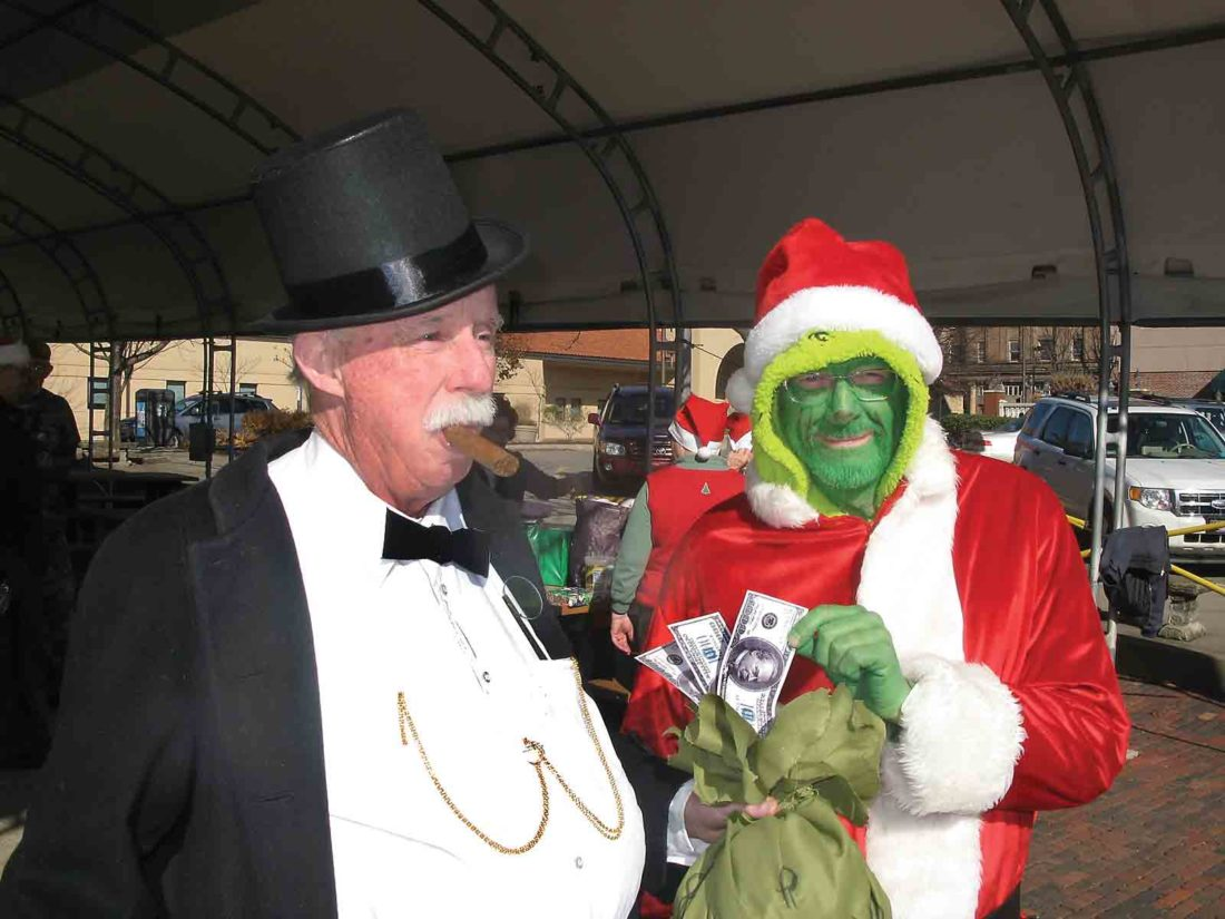 Photo by Jess Mancini From left, Mr. Money Bags, played by Turner Sharp, accepts a bag of money from the Grinch, portrayed by Bill Schleier, on Friday during a protest of the pending tax bill in Congress by Wood County Indivisible.