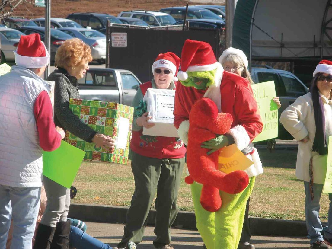 Photo by Jess Mancini The Grinch sneaks away with a Christmas present representing the Children's Health Insurance Program, one of the programs that would be eliminated under the tax reform bill pending in Congress, according to Wood County Indivisible, which organized a protest rally on Friday.