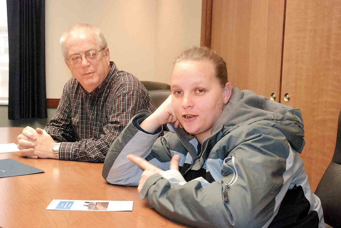 Homecrest Manor resident Ami Bentz, right, talks about the Family Self-Sufficiency Program she and her husband, David, recently completed Friday at the Parkersburg Housing Authority offices as FSS coordinator Kyle Mann listens. (Photo by Evan Bevins)