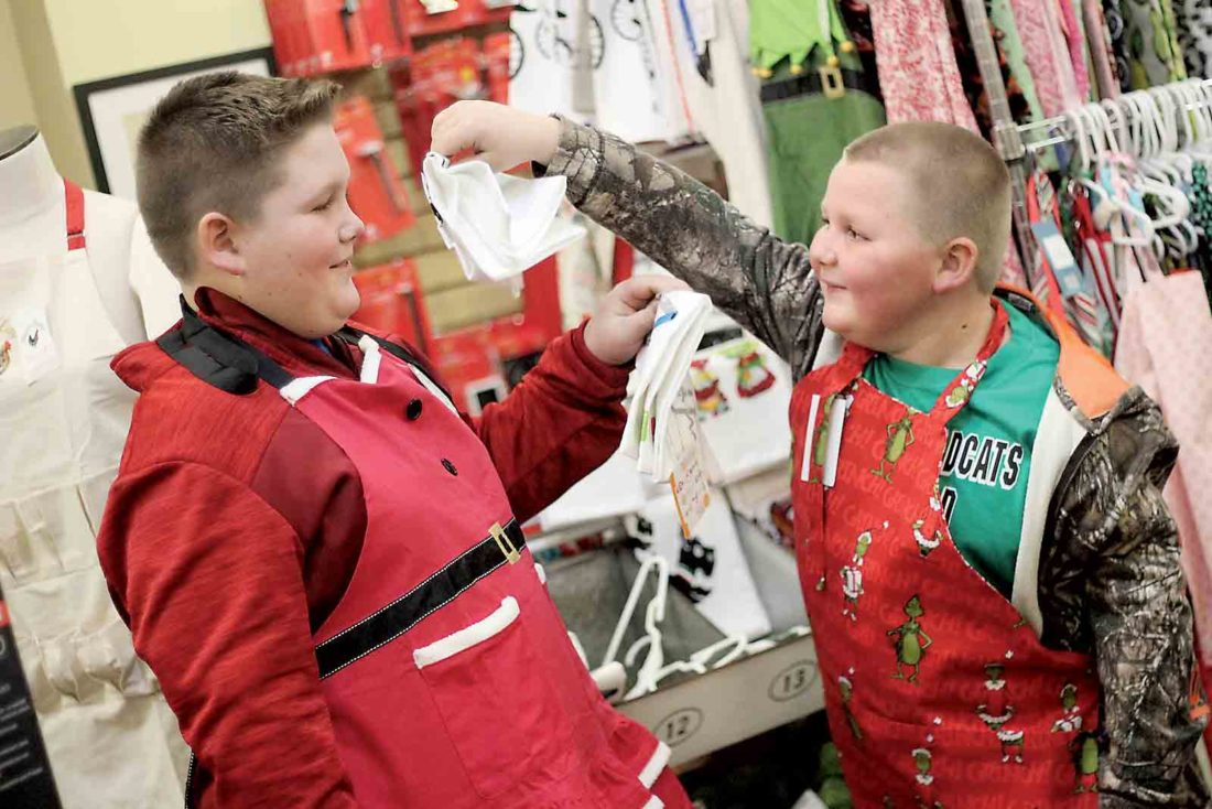 Photo by Janelle Patterson Dalson Green, 11, left, and his brother Austin, 8, try on Christmas aprons at The Cook's Shop in Marietta Friday during Moonlight Madness.