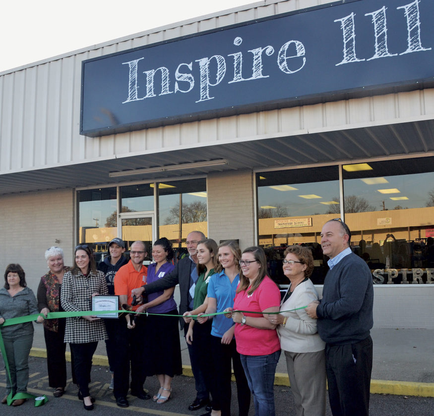Photo by Brett Dunlap The owners and employees of the new Inspire 111 store at the Washington Square Shopping Center join with Belpre Chamber of Commerce officials and Belpre Mayor Mike Lorentz for a ribbon cutting for their new store.
