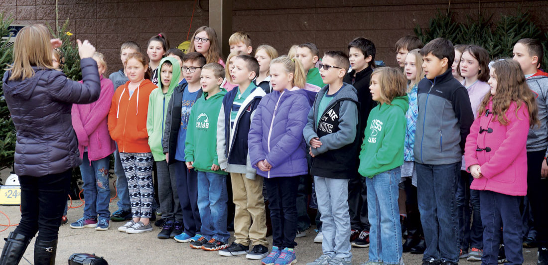 Photo by Michael Erb Criss Elementary School fourth- and fifth-grade students, under the direction of music teacher Becky Blauser, sing the national anthem Wednesday during a ribbon-cutting ceremony at the 7th Street Kroger.
