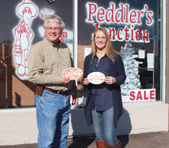 Photo Provided Bob Rauch, chairman of Belpre Area Chamber of Commerce Economic Development Committee, and Ashley Tanner, member of the Tanner family, owners of Peddler's Junction, display special Buy Belpre decals for cars and windows.