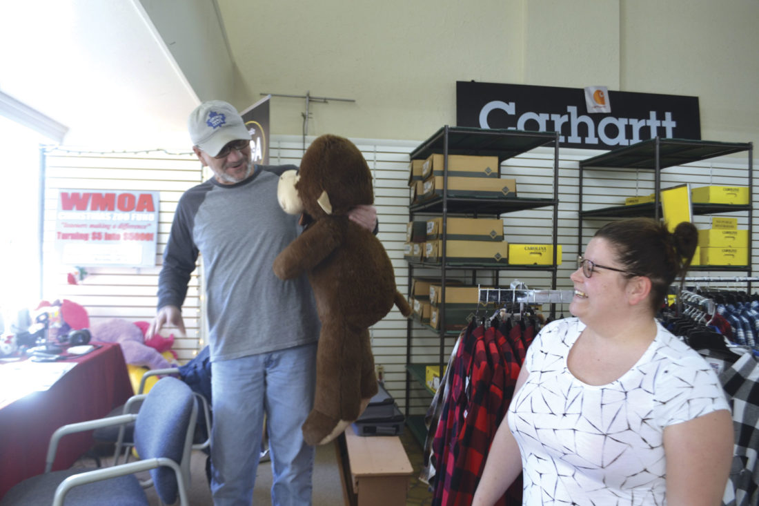 Photo by Michael Kelly WMOA 1490 AM radio personality Kyle Wenzel accepts the gift of stuffed toy bears from Lauren Allen and Carol Wolfe of Belpre in the display window of The Workingman's Store at 109 Putnam St. The radio station will take contributions of cash or stuffed animal toys through Dec. 22 for distribution as Christmas gifts to needy children.