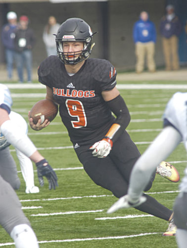Martinsburg quarterback Tyson Bagent surveys his running path near the goal line Saturday during the Bulldogs' 44-16 Class AAA state championship game win over Spring Valley. Bagent and the Bulldogs won their second straight championship at Wheeling Island Stadium. Photo by Joe Albright.