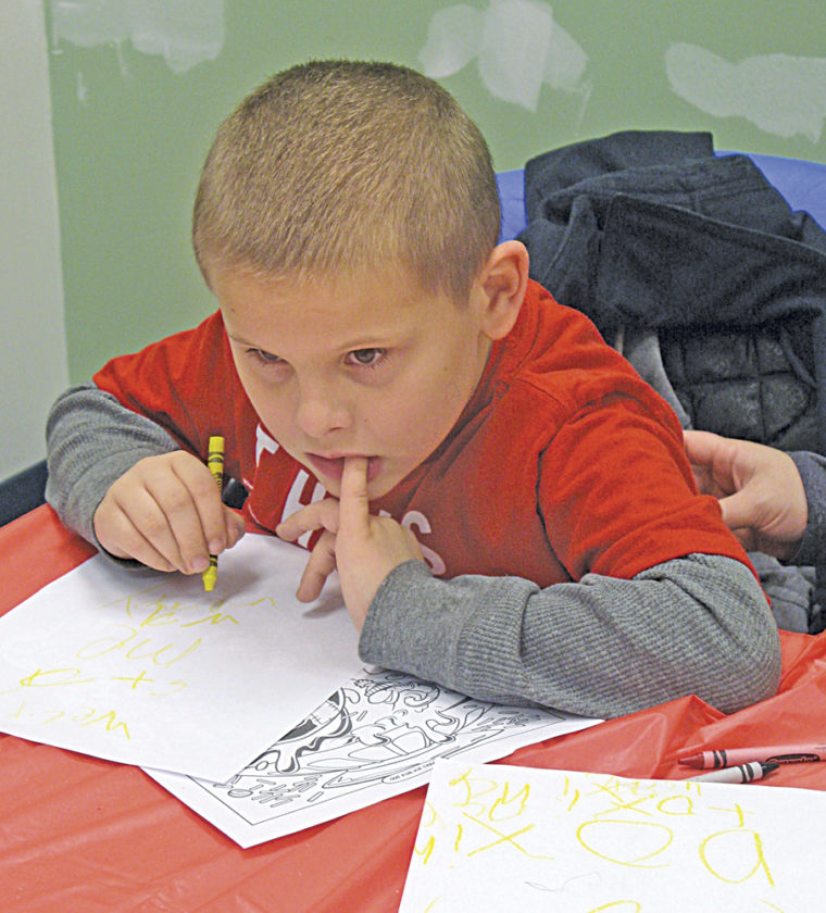 Photo by Jeffrey Saulton Ryan Victory,  of Parkersburg, concentrates on a drawing during the Sheetz Coloring Contest in the Judge Black Annex during the 2017 Winterfest.